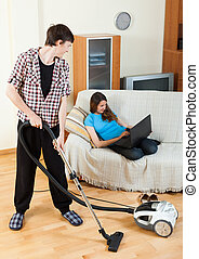 Guy doing house cleaning during girl resting over sofa
