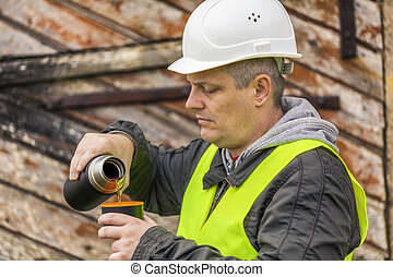 Worker pouring tea near old wooden