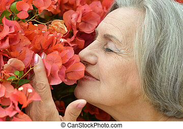 cute older woman - Happy cute older woman with pink flowers