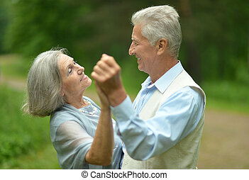 Happy mature couple walking in the park in the afternoon