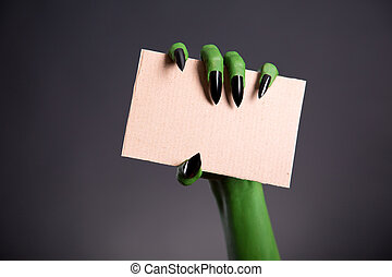 Green monster hand with sharp nails holding blank piece of...