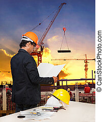 engineering man working in building construction site against be