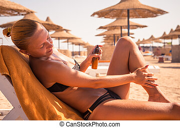 Sensuous slim woman applying suntan oil - Sensuous slim...