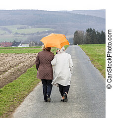 women in rain under an umbrella in rural landscape