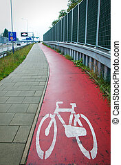 Red bicycle path. Sign of a bike.