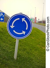 Roundabout traffic sign over grass
