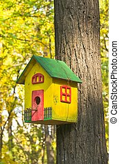 funny colorful birdhouse in the autumn garden