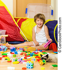 Happy 4 years child playing with toys in home interior