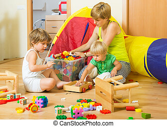 Children and mother collecting toys in plastic box
