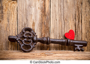 Key. - Old vintage key with heart on wooden background.