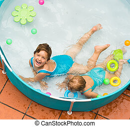 Children swimming in kid pool - Happy laughing children...