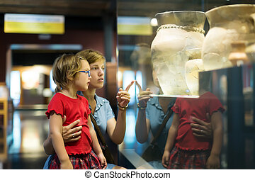 mother and child looking old amphores in museum - mother and...