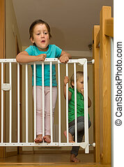 Two girls approaching safety gate of stairs - Two little...