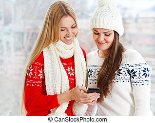 Happy girls using app on a mobile phone