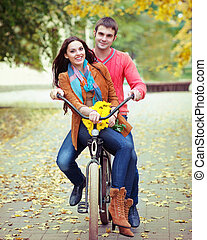 Happy couple with bicycle in autumn park - Happy young...
