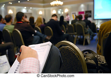 seminar - business man taking notes on seminar conference