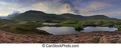 Stunning sunrise panorama landscape of heather with mountain...