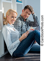 Middle Age Couple Sitting on Floor Looking at Cam - Close up...