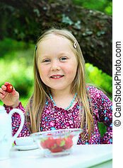 Smiling little girl at tea party - A close-up of a smiling...