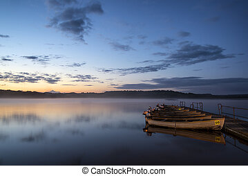 Beautiful landscape sunrise over still lake with boats on jetty