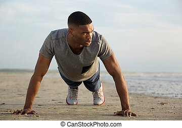 Young guy doing push ups at the beach - Portrait of a young...