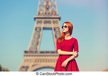 Beautifu girl in Paris with Eiffel tower on background.