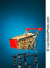 shopping cart full of money, blue background