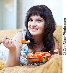 Casual woman eats  salad