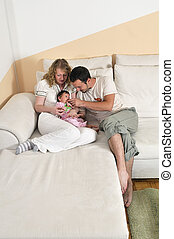 indoor portrait with happy young family and  cute little babby