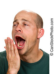 Sleepy Man Yawning - Man covers his mouth with his hand as...