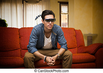 Young man in 3d glasses sitting watching television - Young...