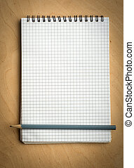 notebook with pencile on a wood background
