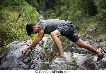 Man Clambering Over Rocky Terrain - Side View of Man...