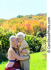 Mother and Child Hugging at Autumn Apple Orchard