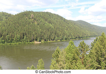 Forested hills and flowing river - riverbank in the city of...
