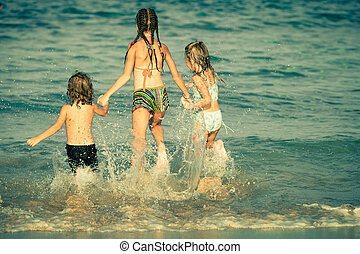 happy kids playing on beach at the day time
