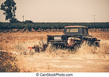 Junk Aged Pickup on the Dry California Meadow. History of...