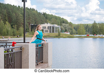 Beautiful girl in a blue dress strolls along the river on...
