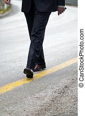 businessman walking on yellow line - businessman walking on...