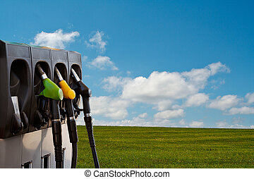 Energy and nature - Three gas pump nozzles over a nature...