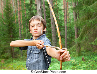 Kid with homemade bow and arrow - Boy aiming home-made...