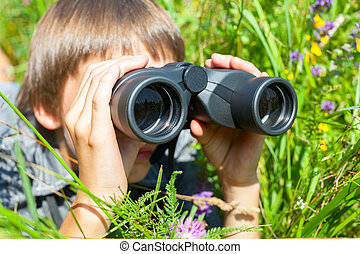 Child looking through binoculars - Boy hiding in grass...