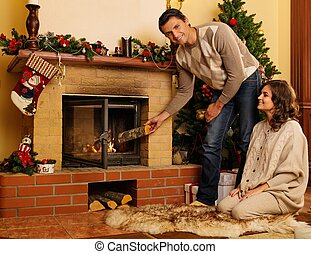Couple putting log into fireplace in Christmas decorated...