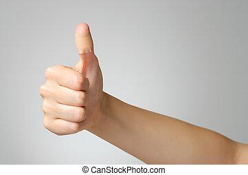 Plaster on female thumb - Female thumb with adhesive bandage