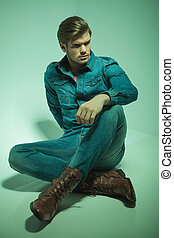 fashion man sitting while resting his hand on his knee - Hot...
