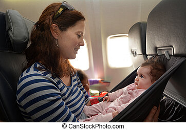 Mother carry her infant baby during flight.Concept photo of...