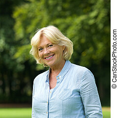 Portrait of a smiling senior woman outdoors - Close up...