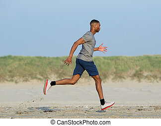 African american man jogging at the beach - Side view of an...