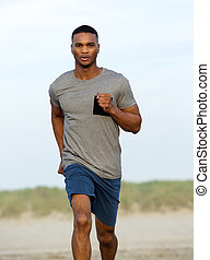 Healthy young black man running outdoors by the beach