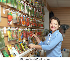 mature woman chooses packaged seeds - Smiling mature woman...